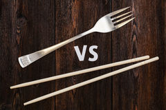 Wooden pairs of chopsticks vs fork. Abstract conceptual image Stock Photo