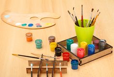 Palette and box with colorful paints and cup with paintbrushes Royalty Free Stock Photos