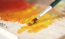 The brush blends the paint in orange color. The wooden palette is painted with yellow and red oil paint. The brush blends the paint in orange color stock images