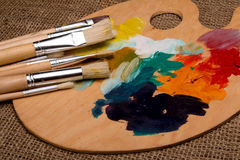 Wooden palette with paints and brushes. And colors Royalty Free Stock Images
