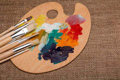 Wooden palette with paints and brushes. Wooden palette with mix paints and brushes Royalty Free Stock Photography