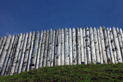 The wooden palisade on the green grass shaft of the ancient fort Royalty Free Stock Photos