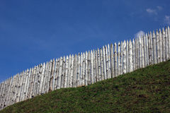The wooden palisade on the green grass shaft of the ancient fort Royalty Free Stock Images