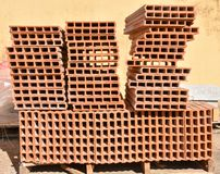 A wooden pallet plenty of old stacked red bricks in rows. Behind there is other pile of red bricks wrapped with plastic. Horizontal photo royalty free stock photo