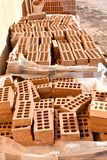 A wooden pallet plenty of old stacked red bricks in rows. Behind there is other pile of red bricks wrapped with plastic. Horizontal photo stock image