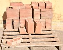 a wooden pallet plenty of old stacked red bricks in rows. Behind there is other pile of red bricks wrapped with plastic royalty free stock image