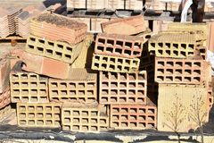 A wooden pallet plenty of old stacked red bricks in rows. Behind there is other pile of red bricks wrapped with plastic. Horizontal photo royalty free stock photos