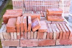 A wooden pallet plenty of old stacked red bricks in rows. Behind there is other pile of red bricks wrapped with plastic. Close up of a wooden pallet plenty of royalty free stock photo