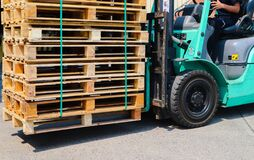 Wooden pallets stack at the freight cargo warehouse for transportation and logistics industrial, Driver forklift loading