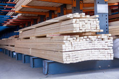 Wooden panels stored inside a warehouse. Wooden panels stored inside an industrial warehouse on metal shelving for use in construction and building, nobody in Stock Image