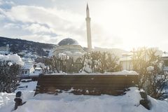 Wooden park bench covered with snow in front of sinan pasha mosq. Ue at Prizren, Kosovo in winter season Stock Photo