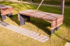 Wooden park bench in garden Stock Photos
