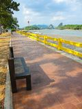 Wooden park bench on red brick path way with scenic waterfront mountain view in Krabi, Thailand. stock photos