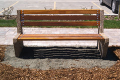 Wooden park bench sitting on grey gravel and mulch. A wooden park bench with grey gravel underneath and brown mulch in front Stock Image