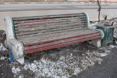 Wooden Park bench standing in the street, paint peeling in front of the bench, there`s a gray Packed snow. Standing next to the li. Shabby old bench standing in Royalty Free Stock Photos