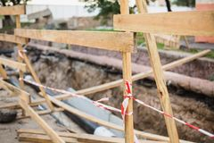 Wooden partition for security. Water pipes with insulation lie on the ground. Stock Photography