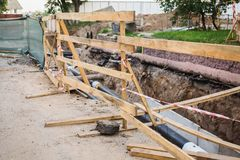 Wooden partition for security. Water pipes with insulation lie on the ground. Stock Photo