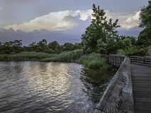 Wooden path along a body of water in New Jersey. Wooden path along ripples on a bay in a new jersey park royalty free stock photo