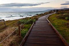 Wooden path along side the sea at sunset Stock Image