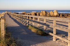 Wooden path with fence to the beach. Walkway on seashore in the morning. Atlantic Ocean coast in Portugal. royalty free stock photography