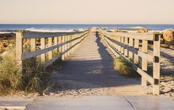 Wooden path with fence to the beach. Walkway on seashore in the morning. Atlantic Ocean coast in Portugal. stock photography