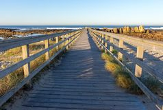 Wooden path with fence to the beach. Walkway on seashore in the morning. Atlantic Ocean coast in Portugal. stock image