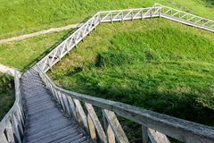 Wooden walking path. Wooden Path in the Garden.  Wooden stairs in the wilderness down to the hill Stock Photo