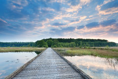 Wooden path on lake water at sunrise Stock Photo