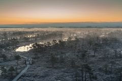 Wooden path, road in swamp on chilly winter morning with frozen trees. And grass. Kemeri national park sunrise with rising fog, Latvia. Vintage look with grain Stock Image
