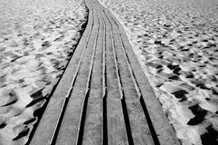 Wooden path through a sandy beach Stock Image