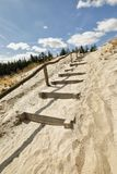Wooden path stairs on sand up to blue sky Stock Photos