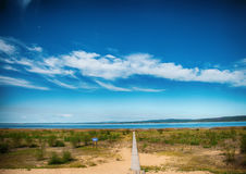 Wooden path to the lake. Sandy shore. Nature in summer. Wooden path to the lake. Sandy shore. A beautiful sky above the lake. Cirrus clouds and a bottomless Royalty Free Stock Image