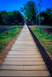Wooden pathway. A bridge made of wood surrounded by green grass and trees royalty free stock images