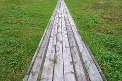Wooden pathway on green grass background Royalty Free Stock Image