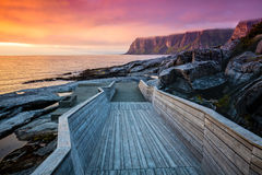 Wooden pathway on the rocky beach. Senja island at orange sunset. Wooden pathway on the rocky beach stock photography