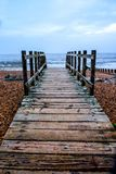 Wooden pathway on Worthing beach. Wooden plank straight pathway on worthing beach, East Sussex Uk pathway is gnarled by the sea on either side of the path are Royalty Free Stock Photography