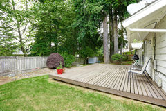 Wooden patio area with deck chairs. Fenced backyard with wooden patio area and two deck chairs royalty free stock photography