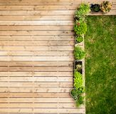 Patio From Above. A wooden patio with flowerpots and a piece of lawn, viewed from above stock photo