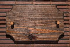 Wooden patterned frame made of wood with a wooden gag is on a bamboo mat. Hard light for hard shadows Stock Images