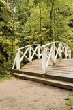 Wooden pedestrian bridge across a small river in an old park in Russia. royalty free stock photo