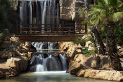 Wooden pedestrian bridge in the park with waterfalls and palm trees. Stock Image
