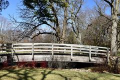 Wooden Pedestrian Bridge. This is a Winter picture of weathered Wooden Pedestrian Bridge over a small creek the meanders through the iconic Robert R. McCormick Stock Photo