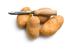 Wooden peeler and potatoes Stock Images