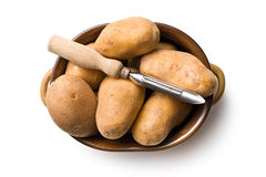 Wooden peeler and potatoes Stock Photography