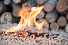 Wooden pellets in flames. Fir pellets inflames in front wooden wall stock images