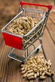 Wooden pellets in shopping cart Royalty Free Stock Photos