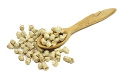 Wooden pellets in a spoon. On a white background Stock Images