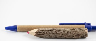 Wooden pencil and pen on the white background. Wooden pencil and brown pen on the white background royalty free stock image