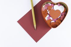 Wooden pencil on an empty red letter near to a box for valentines and different colors inside on a white background Valentine`s d. Ay or festive concept Letter royalty free stock images