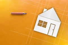 Wooden pencil and house paper cut with yellow background  and co Stock Images